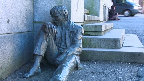 A-homeless-person-sits-near-a-statue-depicting-a-homeless-person-on-the-streets-of-Norway