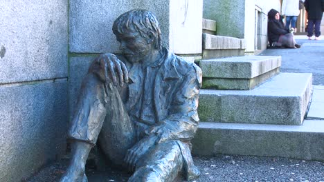 A-homeless-person-sits-near-a-statue-depicting-a-homeless-person-on-the-streets-of-Norway-1