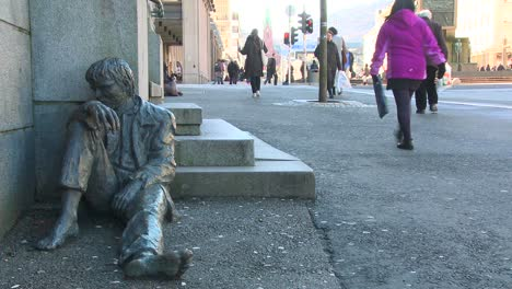 A-homeless-person-sits-near-a-statue-depicting-a-homeless-person-on-the-streets-of-Norway-2