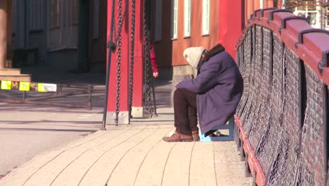 A-homeless-person-sits-on-a-bridge-in-Norway