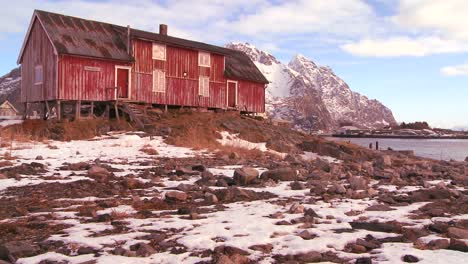 Clouds-moving-behind-a-weathered-red-fishing-village-in-the-Arctic-Lofoten-Islands-Norway