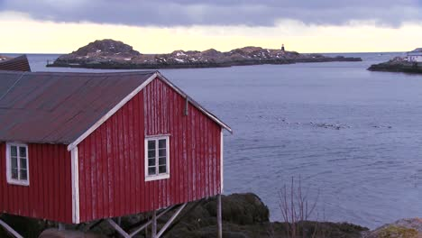 Red-huts-line-a-harbor-and-bay-in-a-village-in-the-Arctic-Lofoten-Islands-Norway