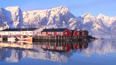 Snowcapped-peaks-loom-behind-a-red-fishing-village-in-the-Arctic-Lofoten-Islands-Norway