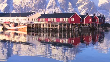Snowcapped-peaks-loom-behind-a-red-fishing-village-in-the-Arctic-Lofoten-Islands-Norway-1