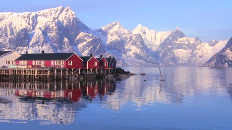 Snowcapped-peaks-loom-behind-a-red-fishing-village-in-the-Arctic-Lofoten-Islands-Norway-2