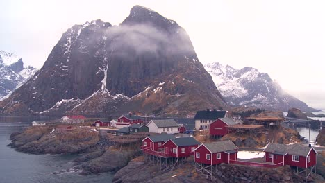 Fog-and-clouds-behind-a-red-fishing-village-in-the-Arctic-Lofoten-Islands-Norway