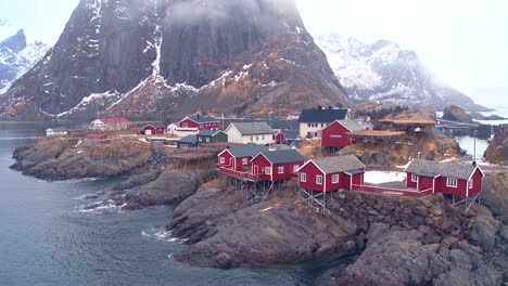 Fog-and-clouds-behind-a-red-fishing-village-in-the-Arctic-Lofoten-Islands-Norway-1