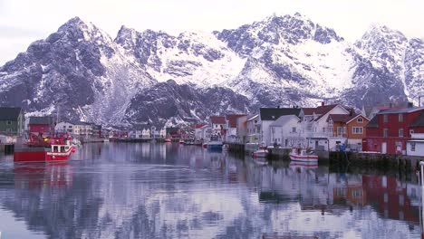 Snow-covered-mountains-are-reflected-in-a-harbor-in-a-small-fishing-village-in-the-Arctic-Lofoten-Islands-Norway