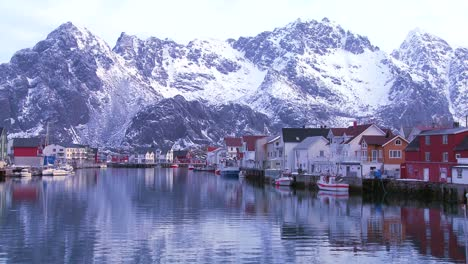Snow-covered-mountains-are-reflected-in-a-harbor-in-a-small-fishing-village-in-the-Arctic-Lofoten-Islands-Norway-1