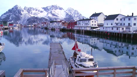 Snow-covered-mountains-are-reflected-in-a-harbor-in-a-small-fishing-village-in-the-Arctic-Lofoten-Islands-Norway-2