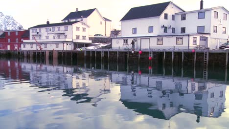 Snow-covered-mountains-are-reflected-in-a-harbor-in-a-small-fishing-village-in-the-Arctic-Lofoten-Islands-Norway-3