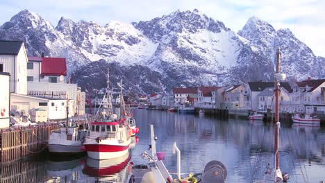 Snow-covered-mountains-are-reflected-in-a-harbor-in-a-small-fishing-village-in-the-Arctic-Lofoten-Islands-Norway-4
