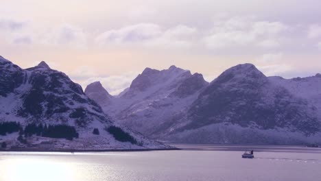 A-fishing-boat-heads-out-to-sea-in-golden-light-in-the-Arctic-Lofoten-Islands-Norway-1