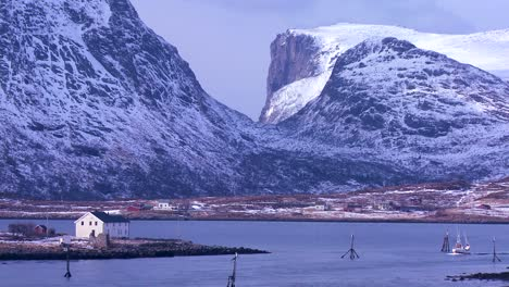A-fishing-boat-heads-through-fjords-in-golden-light-in-the-Arctic-Lofoten-Islands-Norway