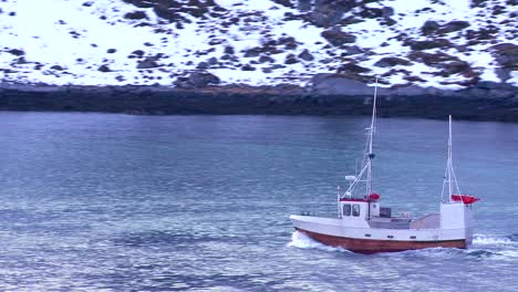 A-fishing-boat-heads-through-fjords-in-the-Arctic-Lofoten-Islands-Norway