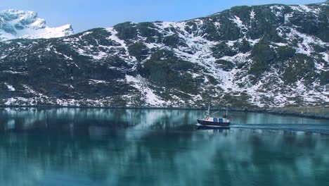 A-fishing-boat-heads-through-fjords-in-the-Arctic-on-glassy-green-water-in-the-Lofoten-Islands-Norway