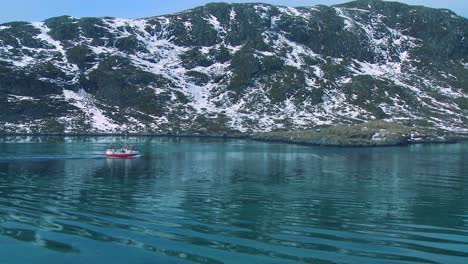 A-fishing-boat-heads-through-fjords-in-the-Arctic-on-glassy-green-water-in-the-Lofoten-Islands-Norway-1