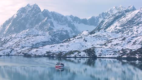 A-fishing-boat-heads-through-fjords-in-the-Arctic-on-glassy-green-water-in-the-Lofoten-Islands-Norway-2