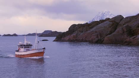 A-fishing-boat-heads-through-fjords-in-the-Arctic-on-glassy-green-water-in-the-Lofoten-Islands-Norway-4