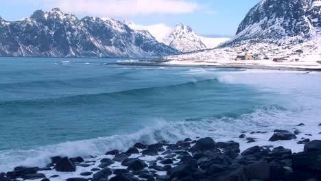 Waves-roll-into-a-beautiful-snow-covered-shoreline-amidst-fjords-north-of-the-Arctic-Circle-in-Lofoten-Islands-Norway-1