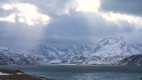 Heavenly-light-streams-down-on-a-beautiful-snow-covered-shoreline-amidst-fjords-north-of-the-Arctic-Circle-in-Lofoten-Islands-Norway-1