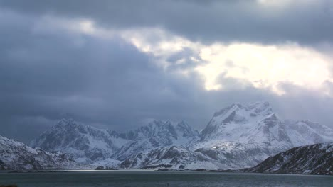 Heavenly-light-streams-down-on-a-beautiful-snow-covered-shoreline-amidst-fjords-north-of-the-Arctic-Circle-in-Lofoten-Islands-Norway-2
