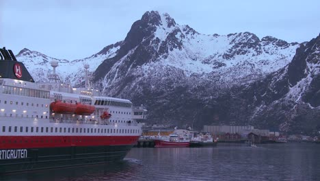 The-cruise-ship-Hurtigruten-sails-through-the-fjords-of-Norway-to-arrive-at-Svolvaer-in-the-Lofoten-Islands