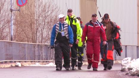 Norwegian-cod-fisherman-walk-down-a-dock-dressed-in-full-gear