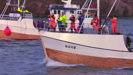 A-large-fleet-of-traditional-commercial-fishing-boats-sails-out-to-sea-of-Norway-in-the-Lofoten-Islands-1