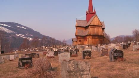 A-cemetery-in-front-of-an-old-wooden-stave-church-in-Norway