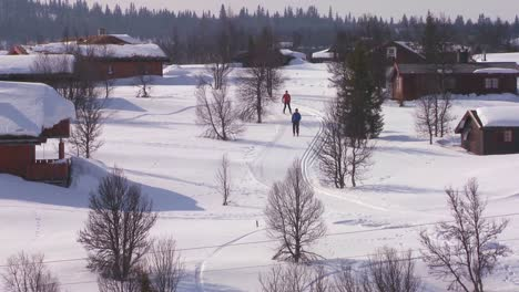 Cross-country-skiers-follow-a-trail-through-a-village-in-Norway