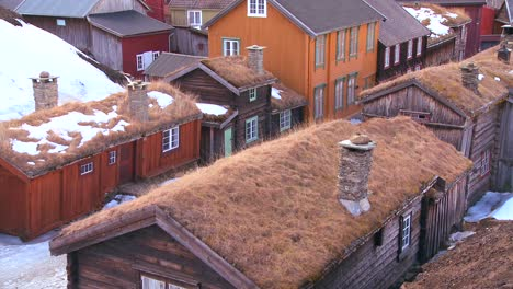 Thatch-roofed-wooden-buildings-line-the-streets-of-the-old-historic-mining-town-of-Roros-in-Norway