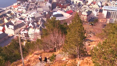 A-jogger-runs-down-a-hill-from-a-high-angle-view-over-the-town-of-Alesund-Norway