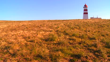 A-pretty-red-and-white-lighthouse-stands-on-a-grassy-hill-in-Norway