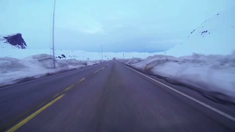 POV-shot-of-a-car-traveling-at-high-speed-along-a-mountain-road-with-ice-and-snow