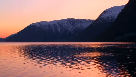 A-perfect-reflection-of-gold-and-red-light-in-a-mountain-lake-at-sunset
