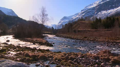 A-beautiful-river-runs-through-a-snowy-fjord-in-Norway