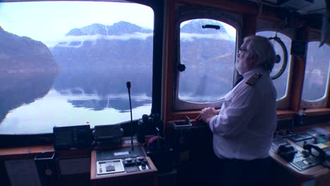 POV-of-a-ferry-boat-with-captain-at-the-helm-as-it-sails-through-mysterious-fog-on-a-fjord-in-Norway