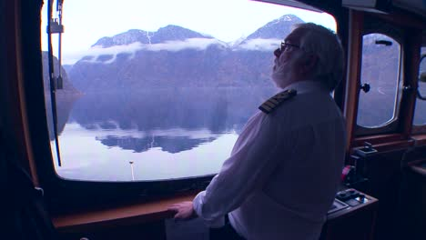 POV-of-a-ferry-boat-with-captain-at-the-helm-as-it-sails-through-mysterious-fog-on-a-fjord-in-Norway-1