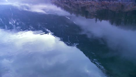 Panning-shot-along-the-water-of-a-fjord-in-fog-in-Norway