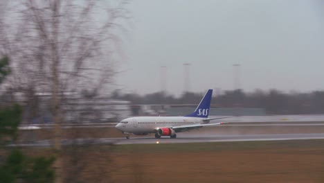 A-plane-comes-in-for-a-landing-at-an-airport-on-a-rainy-day