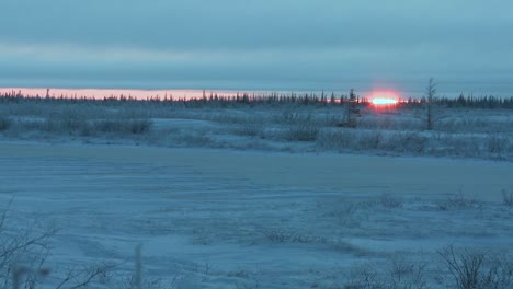 The-sun-rises-behind-a-frozen-highway-across-the-tundra