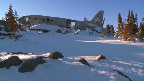 Pan-across-a-crashed-plane-sits-on-a-frozen-snowy-mountainside-in-the-Arctic