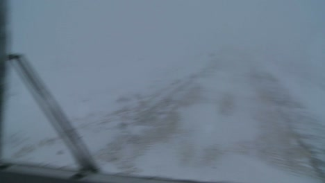 Point-of-view-shot-from-a-tundra-vehicle-of-frozen-tundra-and-barely-visible-road-in-the-Arctic-during-an-intense-blizzard