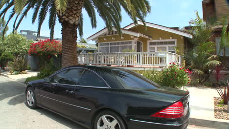 A-black-Mercedes-is-parked-in-front-of-a-quaint-wooden-house-in-Florida-or-California