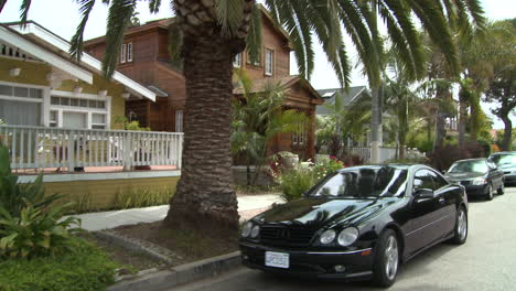 A-black-Mercedes-pulls-up-to-the-curb-on-a-California-or-Florida-street