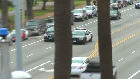 Ein-Polizeiauto-Fährt-Tagsüber-Auf-Einer-Straße-In-Der-Innenstadt-Von-Los-Angeles-Los