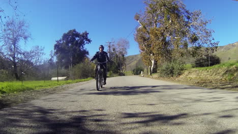 A-man-rides-a-motorized-bicycle-through-the-countryside-on-a-two-lane-road-1