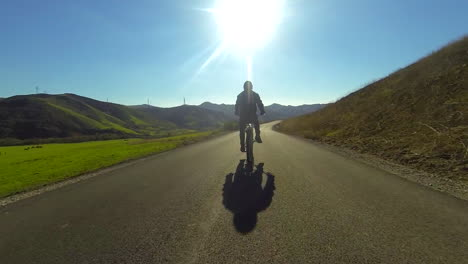 A-man-rides-a-motorized-bicycle-through-the-countryside-on-a-two-lane-road-4