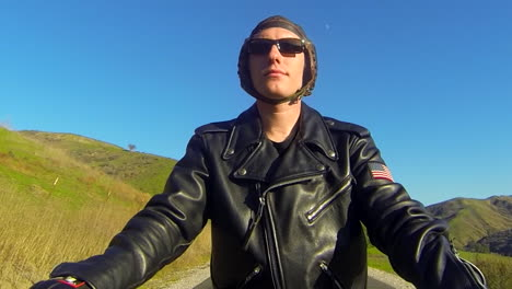 Close-up-of-a-leather-clad-mans-face-as-he-rides-a-motorized-bicycle-through-the-countryside-on-a-two-lane-road